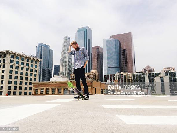 Man standing on rooftop with skateboard
