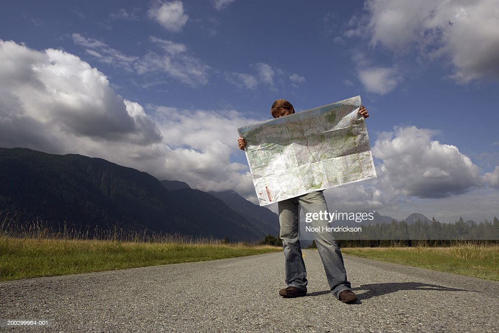 Man standing on rural road reading road map : Stock Photo
