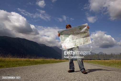 Man standing on rural road reading road map