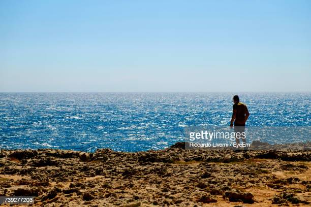 Man Standing On Shore At Beach Against Clear Sky