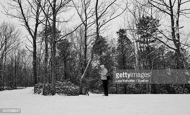Man Standing On Snowy Field In Forest