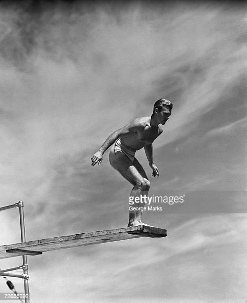 Uomo in piedi sul trampolino, preparando a tuffo, (B & W