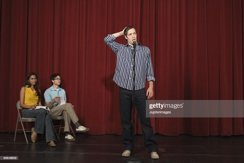 Man standing on stage scratching head