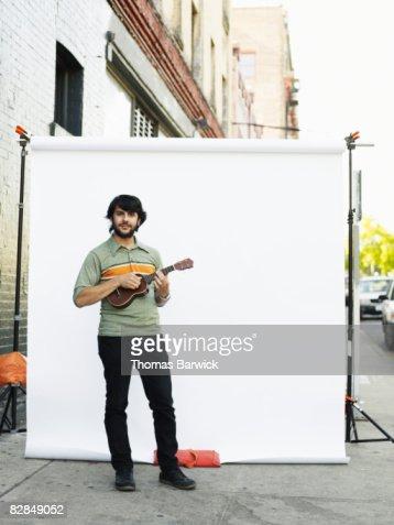 Man standing on street playing ukulele