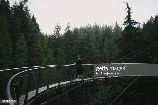 A man standing on the bridge in Capilano park