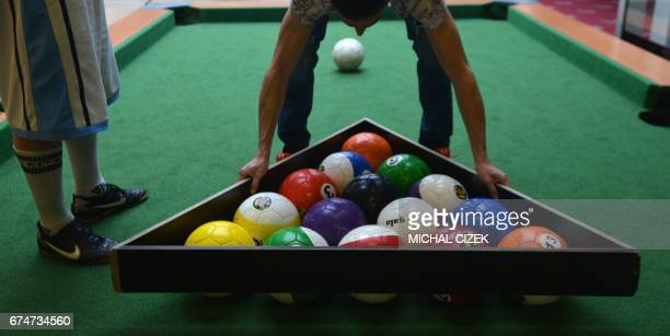 A man standing on the field adjusts the balls at the start of a footballpool match on April 28 2017 in Prague Footballpool is a combination of...