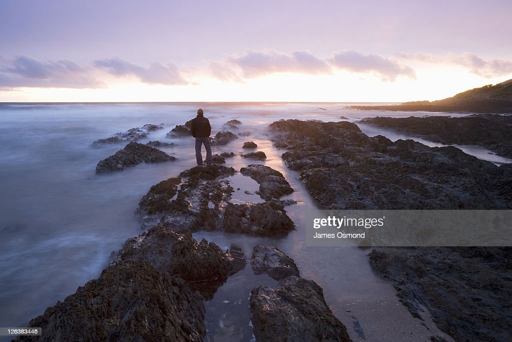 A man standing on the rocks at Croyde Bay looking out to sea at sunset. : Stock Photo