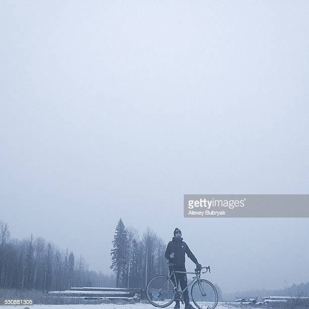 A man standing on the snow road with cyclocross bicycle