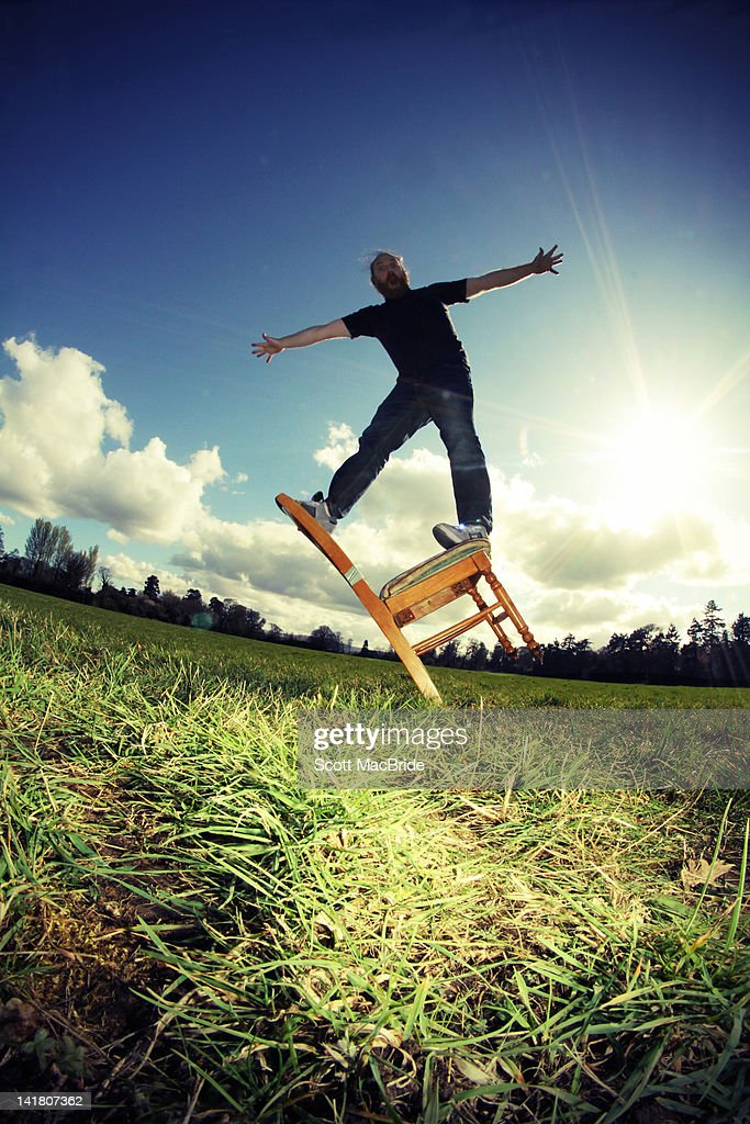 Man standing on tipping chair : Stock Photo