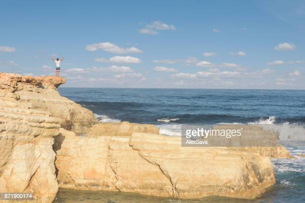 Man standing on top of a cliff at the seaside