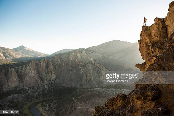 A man standing on top of a tall cliff.