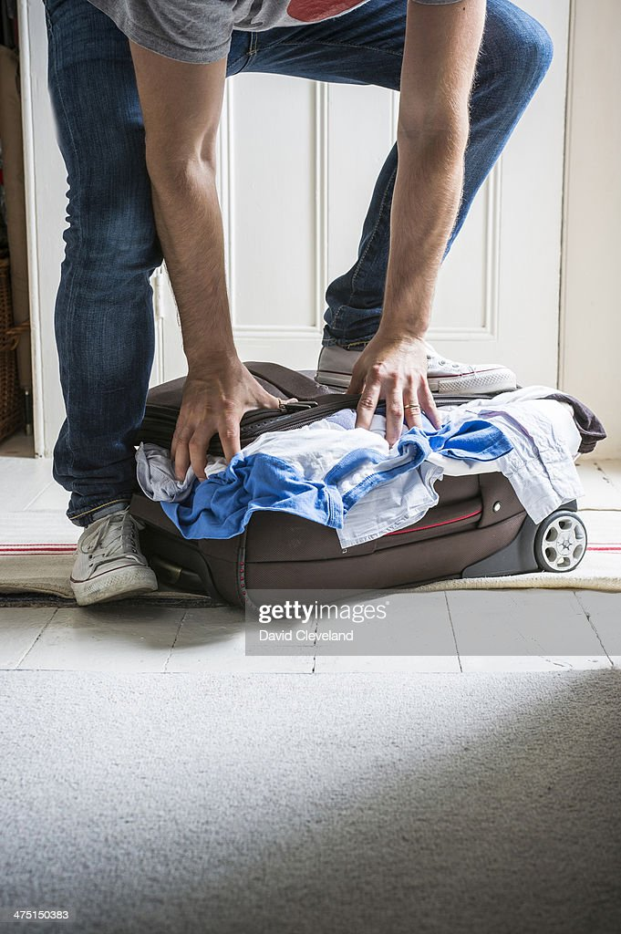 Man standing on top of full suitcase