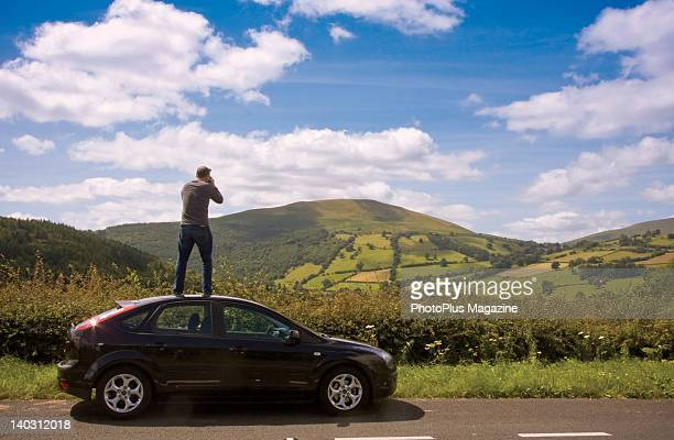 Man standing on top of his car with a camera taking pictures of the countryside taken on July 21 2008