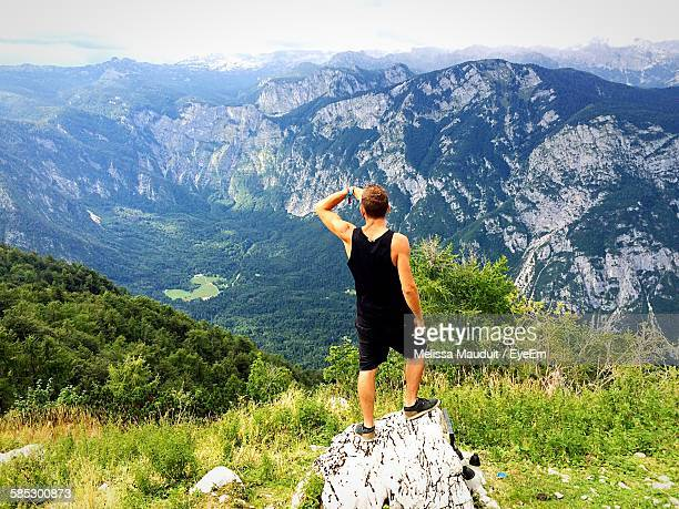 Man Standing On Top Of Rock Looking At Mountains