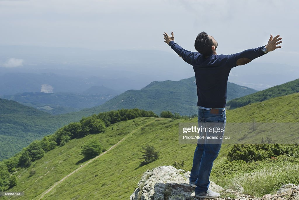 Man standing on top of rock with arms outstretched, rear view : Stock Photo