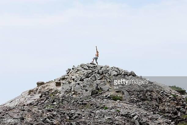 A man standing on top of the rock mountain