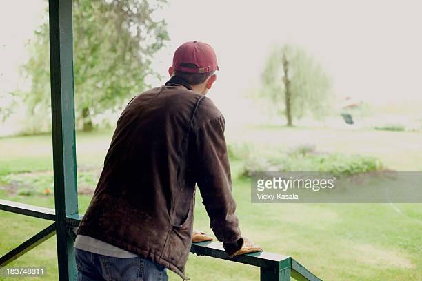 Man standing on verandah looking at garden
