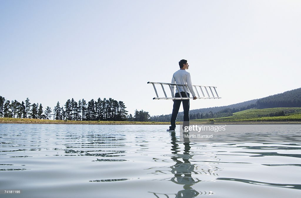 Man standing on water with ladder : Stock Photo