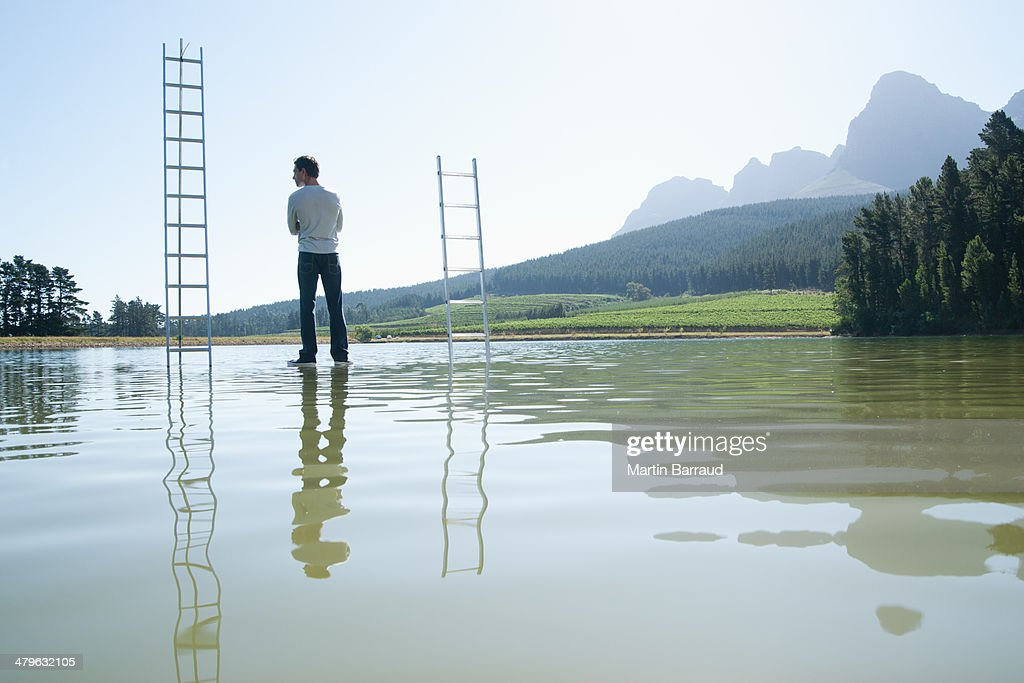 Man standing on water with ladders : Stock Photo
