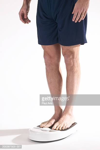 Man standing on weighing scale, low section