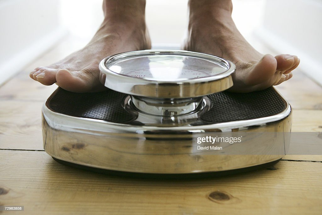 Man standing on weight scale, close-up, low section : Stock Photo