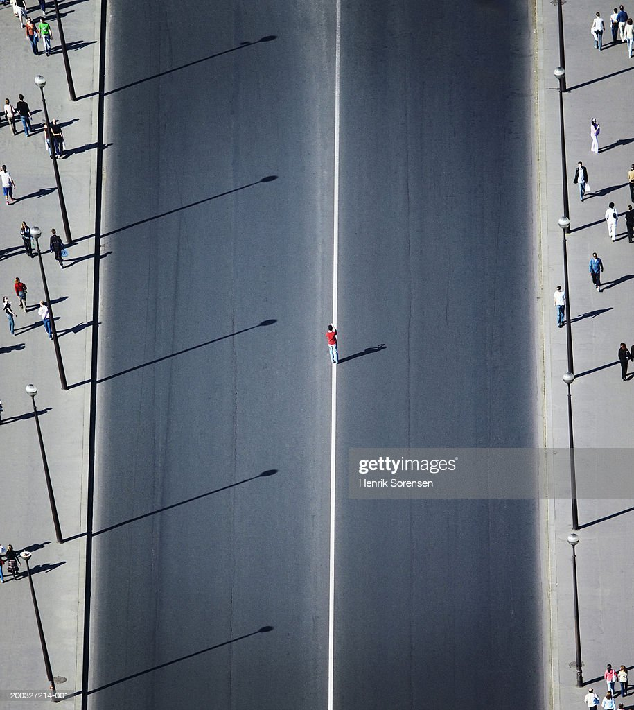 Man standing on white line in middle of road, elevated view : Stock Photo