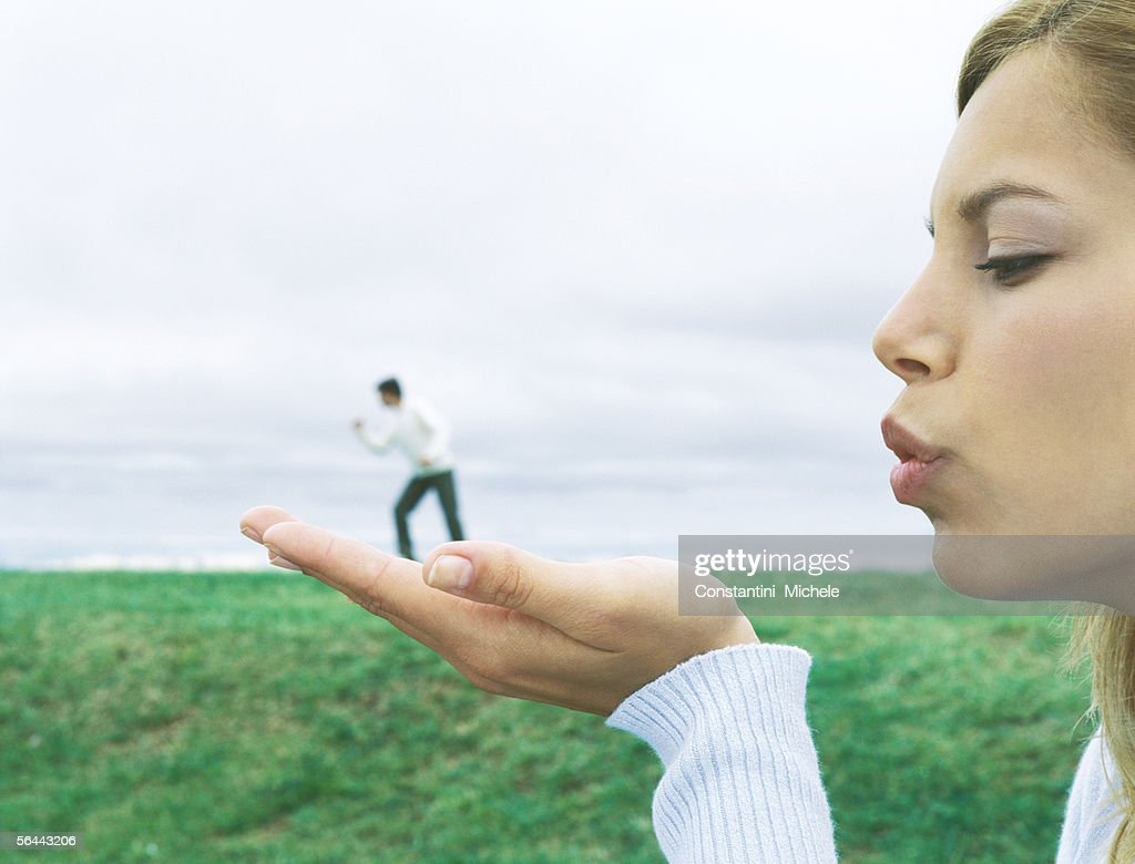 Man standing on woman's hand, optical illusion