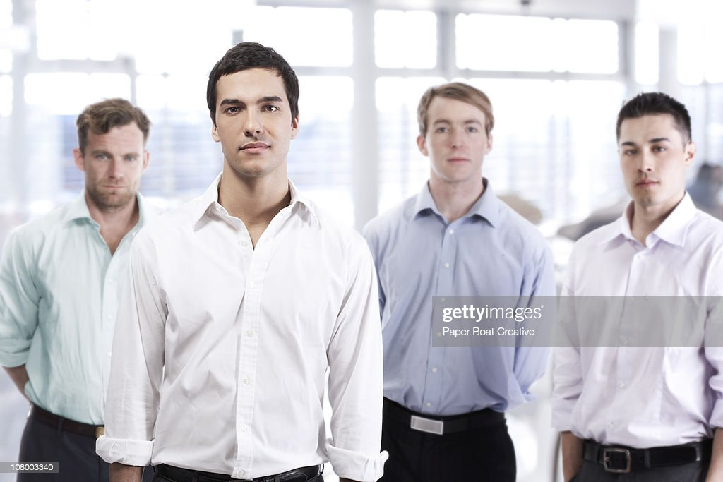 Man standing out from a group of other men : Stock Photo
