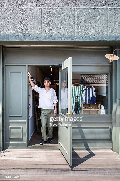 A man standing out front of his shop
