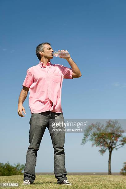 Man standing outdoors drinking from bottle of water, low angle view, full length