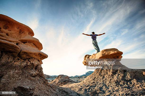 A man standing outdoors on a rock formation in the desert