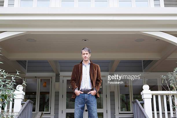 Man standing outside house (portrait, low angle view)