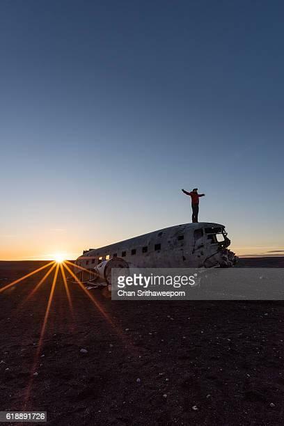 Man standing Over Dakota DC3 plane wreckage in Iceland