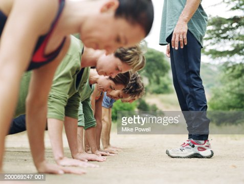 Man standing over group of people doing pushups, side view