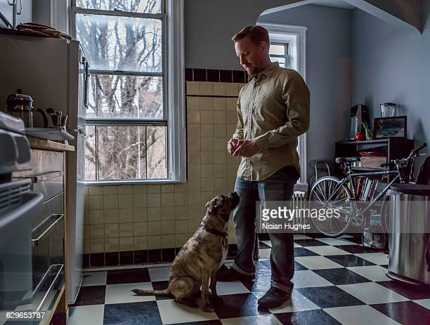 Man standing over his dog in kitchen