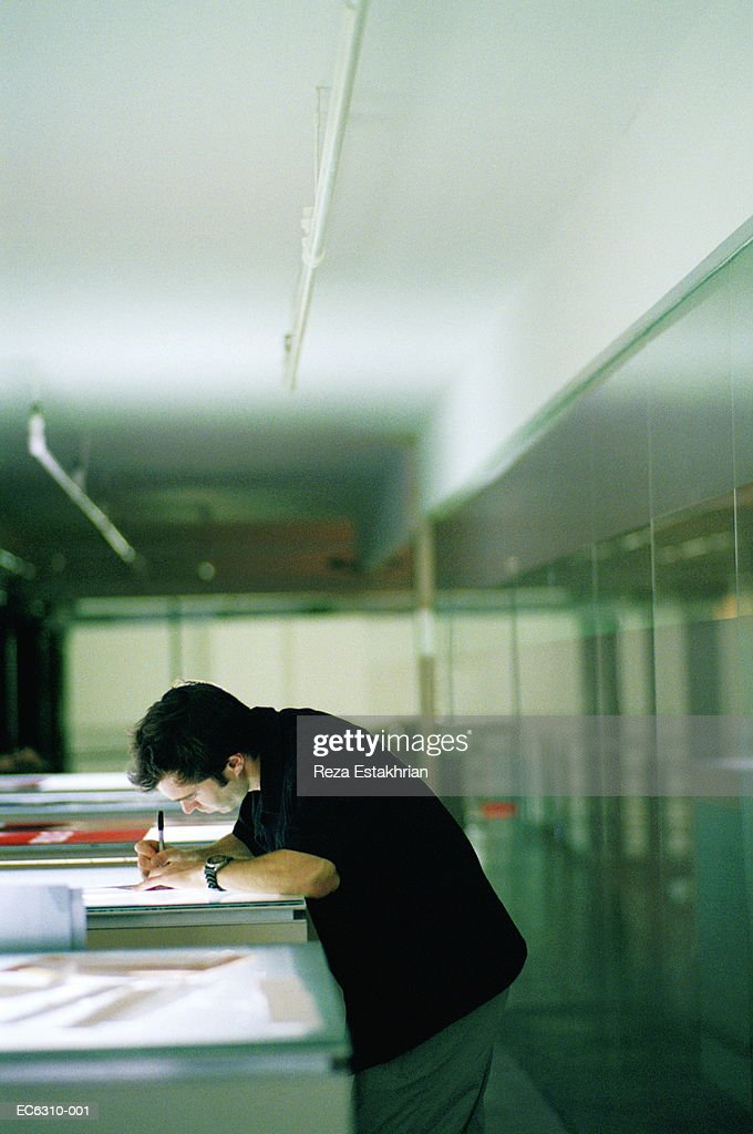 Man standing over lightbox, writing notes : Stock Photo