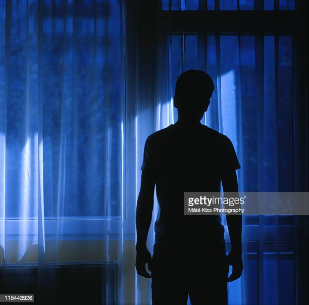 Man standing silhouette in room.