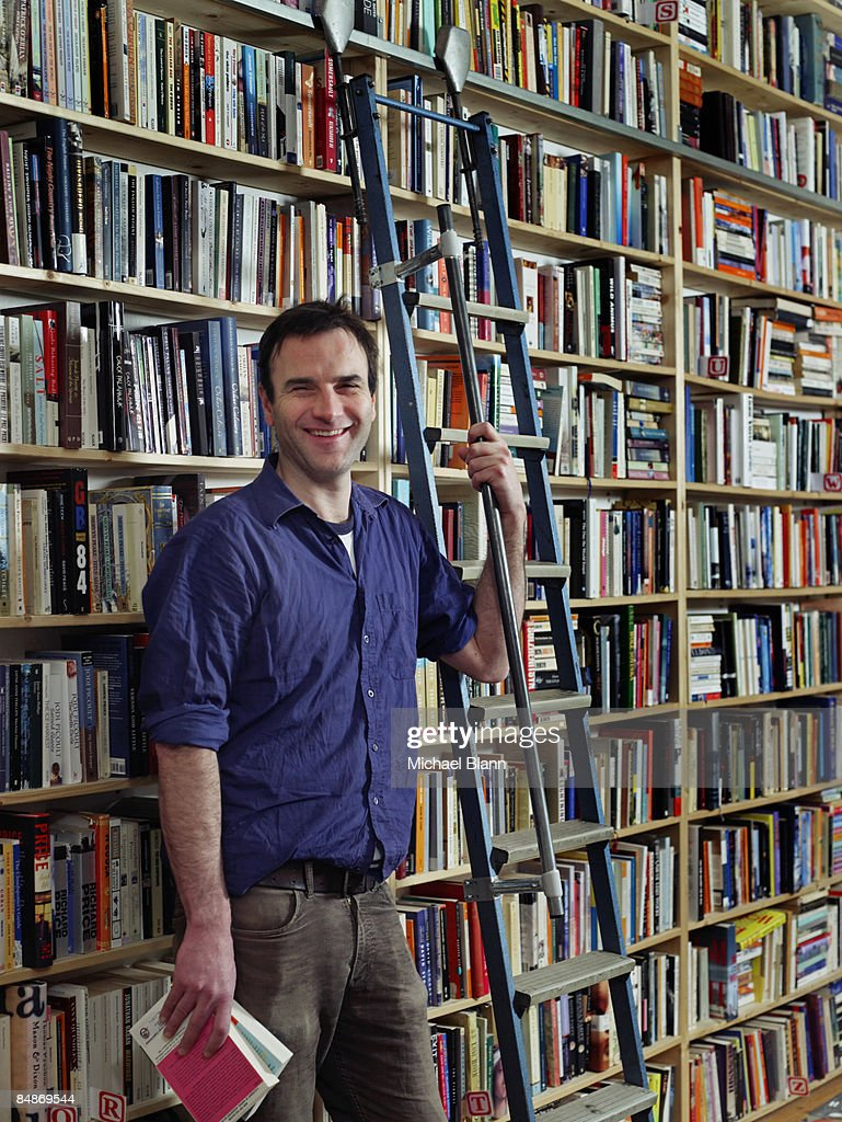 man standing smiling to camera in bookshop : Stock Photo
