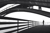Man standing under bridge arch