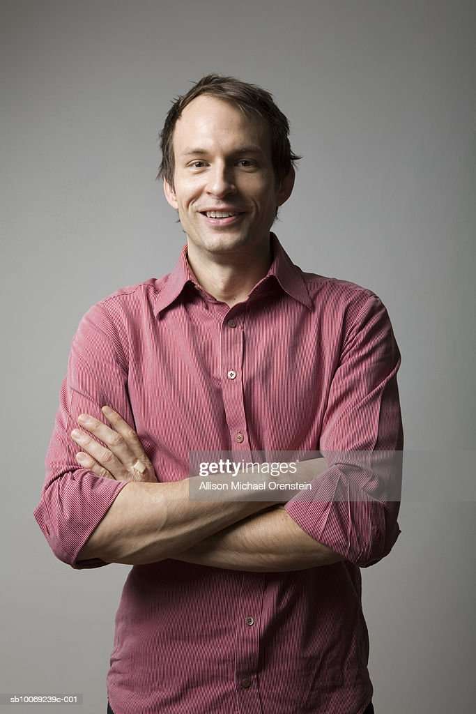 Man standing with arms crossed, smiling, portrait : Stock Photo