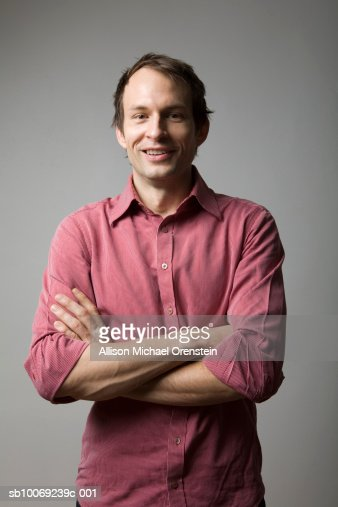 Man standing with arms crossed, smiling, portrait : Foto de stock