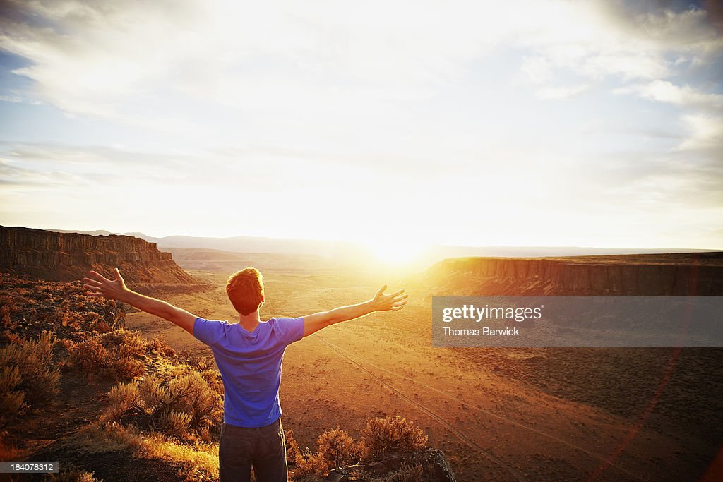 Man standing with arms outstretched at sunset : Stock Photo
