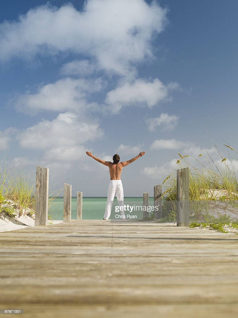 Man standing with arms outstretched on ocean boardwalk : Stock Photo