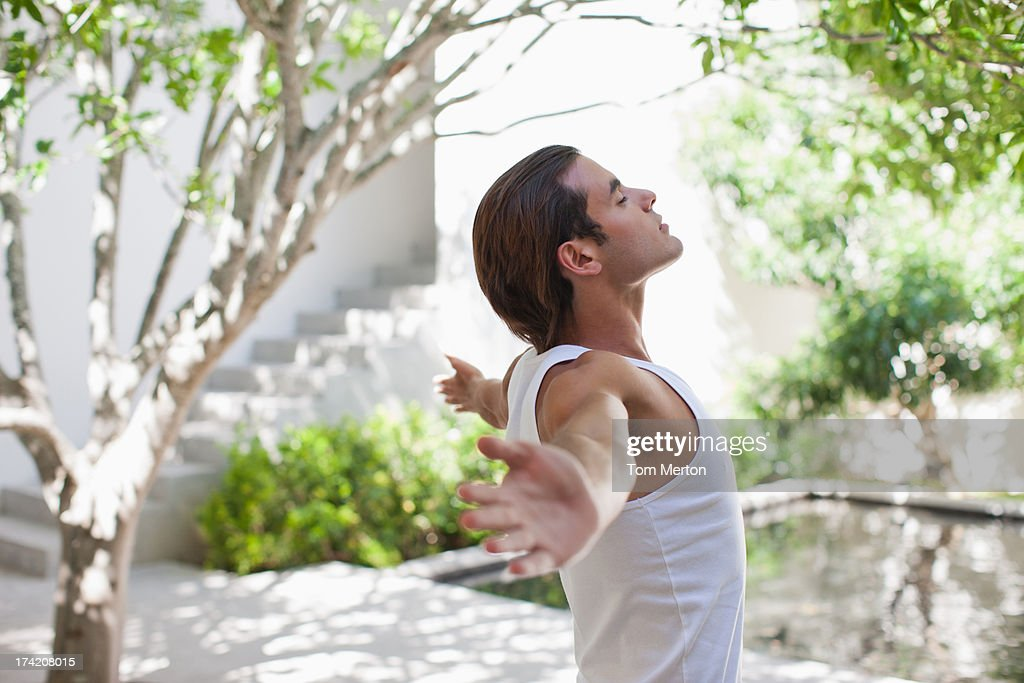 Man standing with arms outstretched : Stock Photo