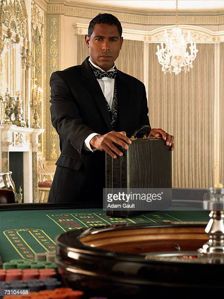 Man standing with briefcase at roulette table, portrait