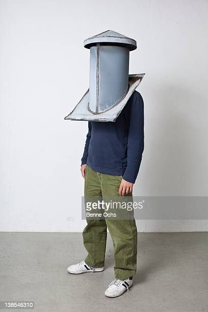 Man standing with chimney cap over his head
