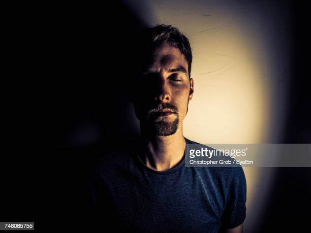 Man Standing With Eyes Closed Against Wall In Room