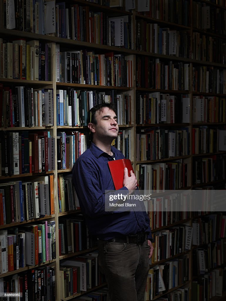 man standing with eyes closed holding in bookshop : Stock Photo