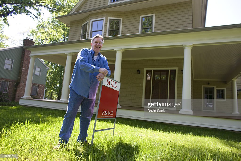Man standing with for sale sign in front of home : Stock Photo