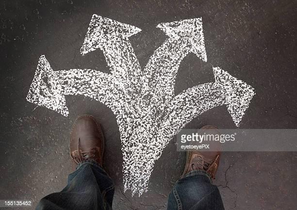 Hombre de pie con cuatro caminos que elegir